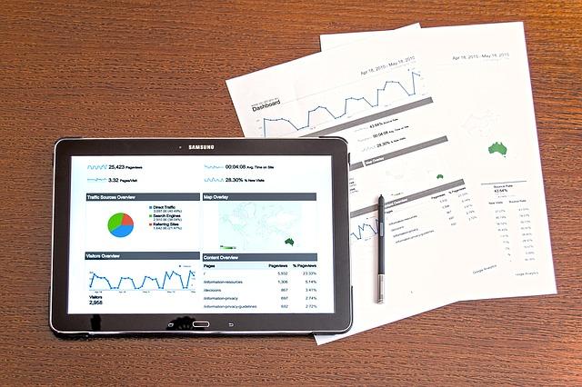 タブレットと資料でデータを示している